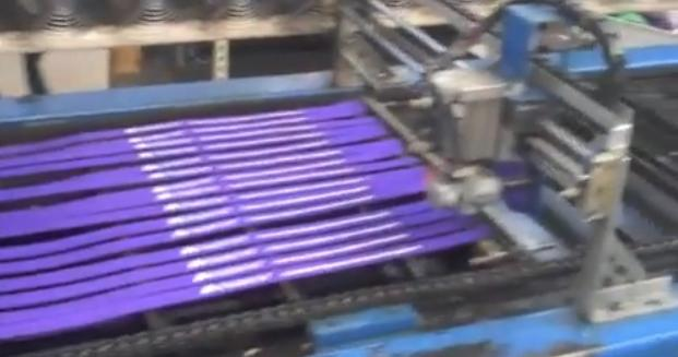 A large, industrial machine that cuts printed lanyards